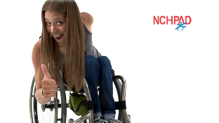 WHite female is leaned over in her wheelchair giving a thumbs up to the camera.